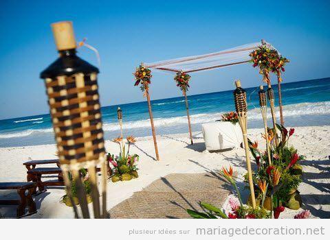 Déco mariage sur la plage, torches et fleurs tropicales